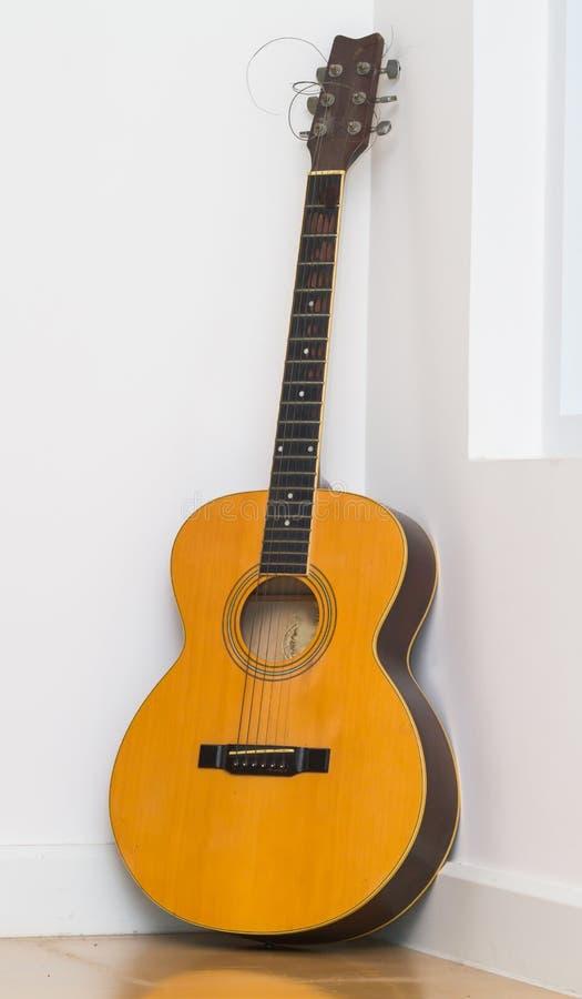 Guitarra vieja que pone en el piso de madera imagen de archivo libre de regalías