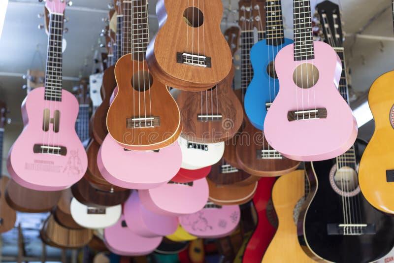 Guitarras à venda penduradas no teto dentro da loja fotografia de stock