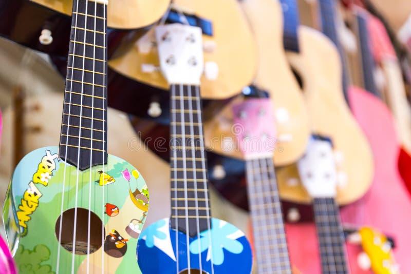 guitarras de madera coloridas que cuelgan en la pared de la sala de exposición de la tienda imagen de archivo