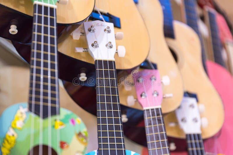 guitarras de madera coloridas que cuelgan en la pared de la sala de exposición de la tienda fotografía de archivo