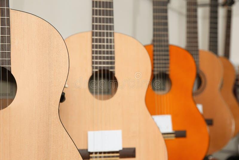 Guitarras de madera modernas en tienda de la música fotos de archivo