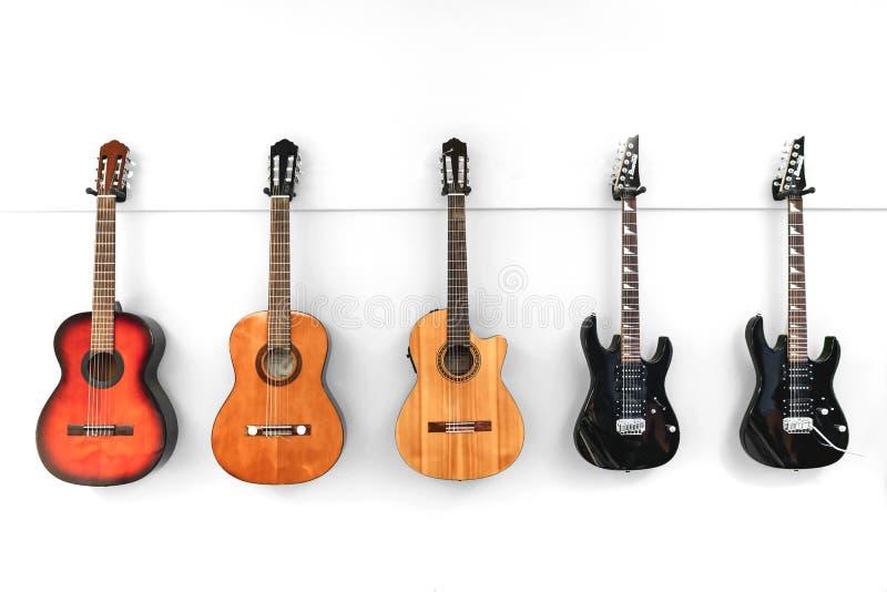 5 guitarras que cuelgan delante de una pared blanca fotografía de archivo libre de regalías