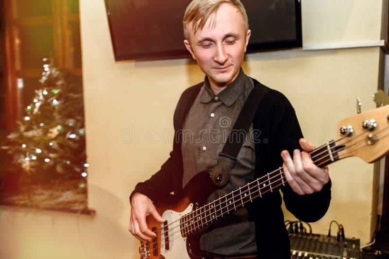 Guitarrista bajo elegante que juega en un concierto en un fondo de h imagenes de archivo
