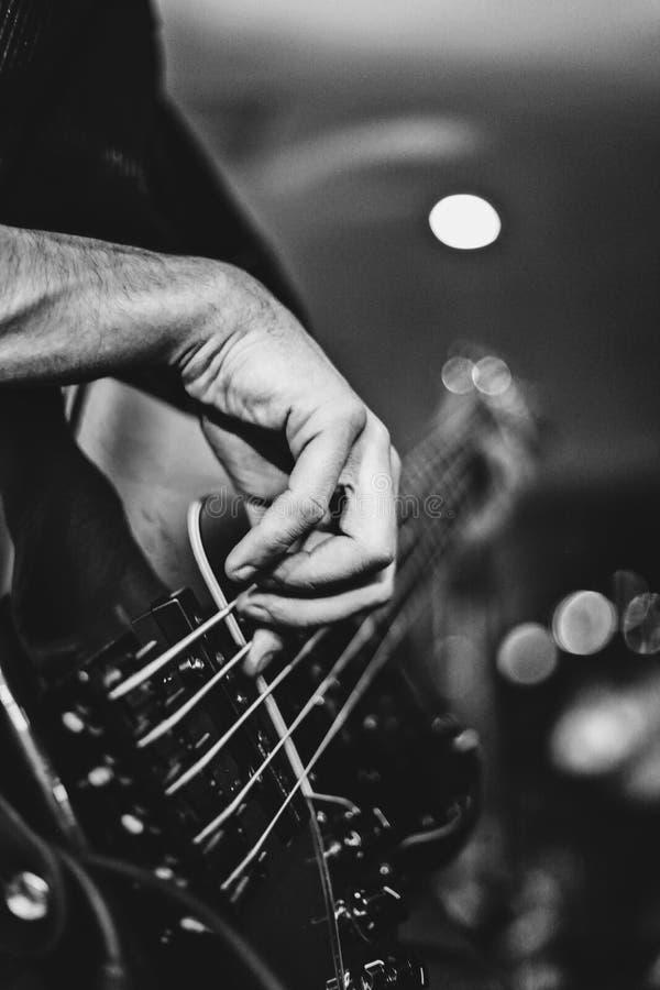 Guitarrista bajo que golpea ligeramente en un bajo de 5 secuencias durante un extracto de la demostración de la roca imagen de archivo libre de regalías