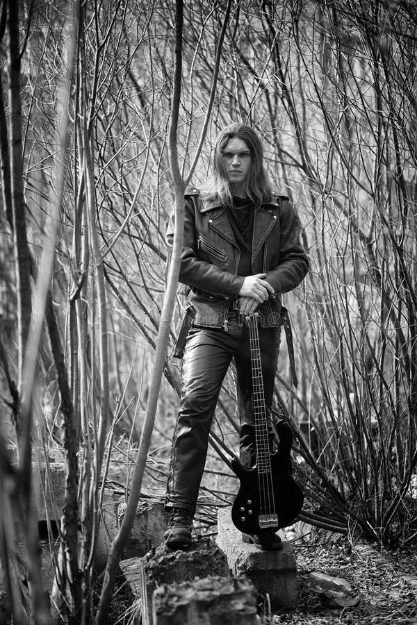 Guitarrista da rocha exterior Um músico com uma guitarra-baixo em um leath imagens de stock