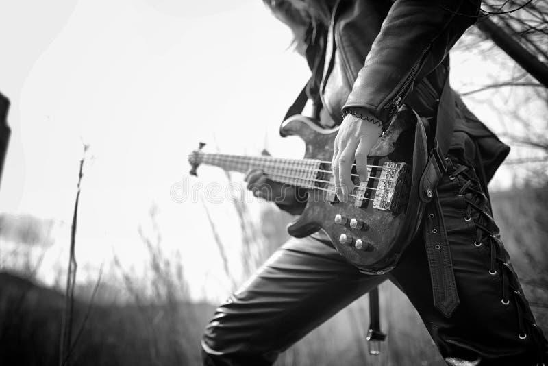 Guitarrista da rocha exterior Um músico com uma guitarra-baixo em um leath imagens de stock royalty free