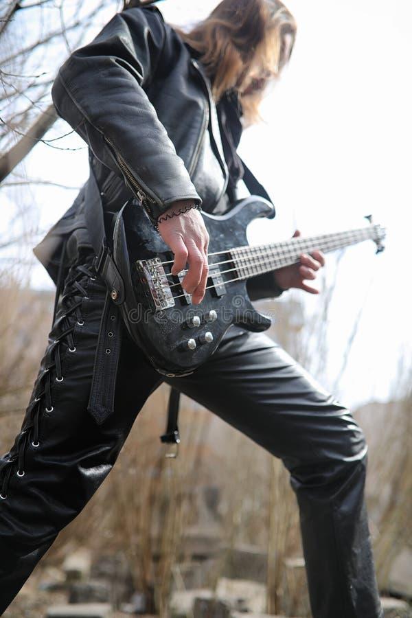 Guitarrista da rocha nas etapas Um músico com uma guitarra-baixo na imagens de stock royalty free