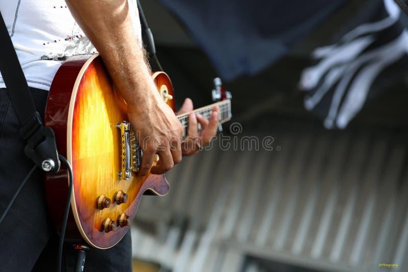 Guitarrista de ligação em um grupo de rock imagem de stock royalty free