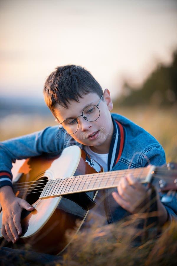 Guitarrista do menino que senta-se no campo menino que joga a guitarra na natureza fotos de stock