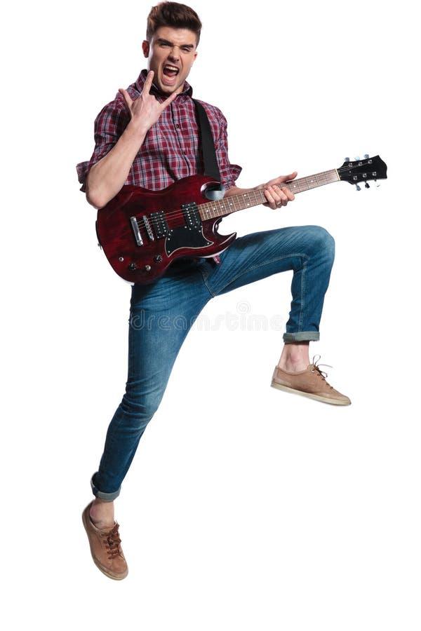 Guitarrista emocionado que salta y que hace la roca en muestra durante concierto imagen de archivo