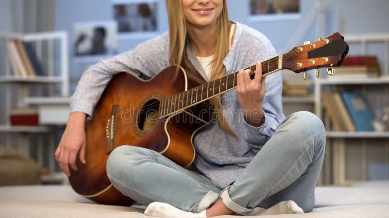 Guitarrista femenino que realiza la canción en casa, afición creativa, preparándose para la audición fotografía de archivo