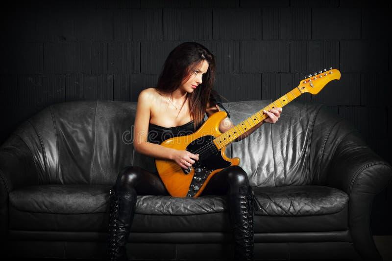 Guitarrista femenino que se sienta en un sofá de cuero foto de archivo libre de regalías