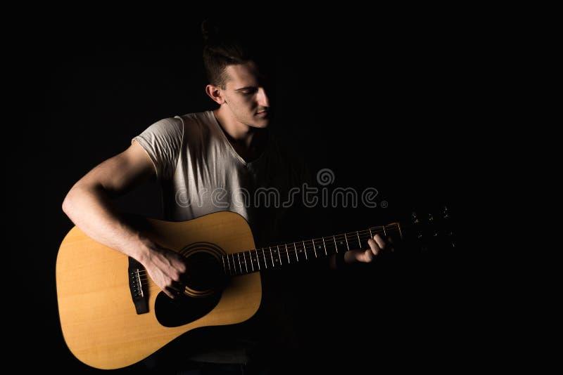 Guitarrista, música Um homem novo joga uma guitarra acústica em um fundo isolado preto Quadro horizontal fotos de stock