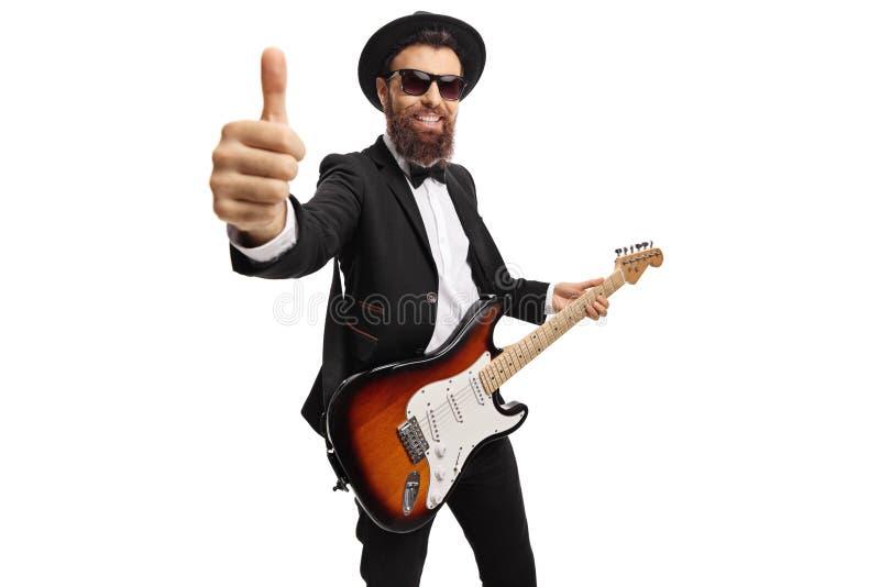 Guitarrista masculino alegre com uma guitarra el?trica que mostra os polegares acima imagem de stock