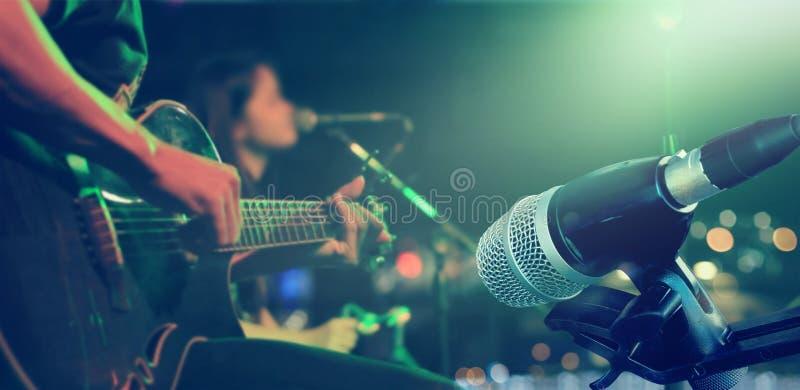 Guitarrista na fase com o microfone para o fundo, macio e o borrão fotografia de stock royalty free