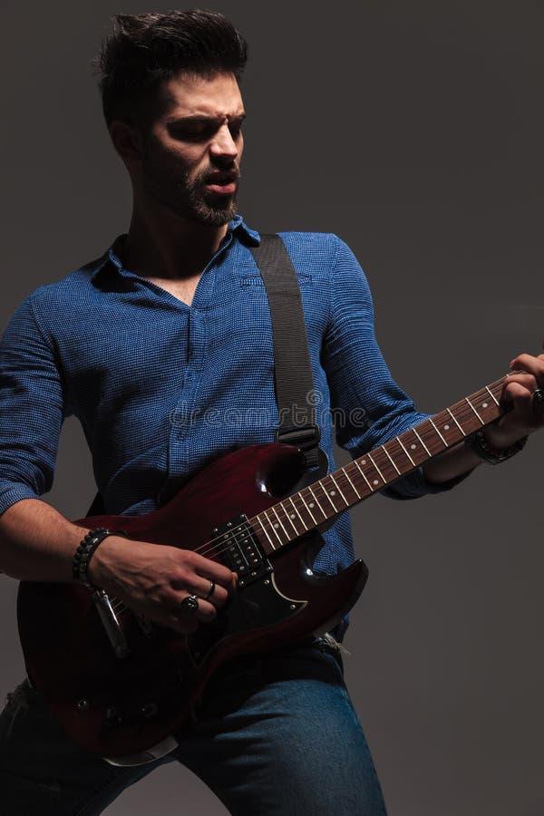 Guitarrista novo apaixonado que joga sua guitarra elétrica fotografia de stock
