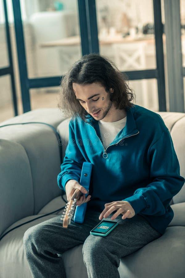 Guitarrista novo atento com o cabelo longo que guarda um instrumento musical imagem de stock
