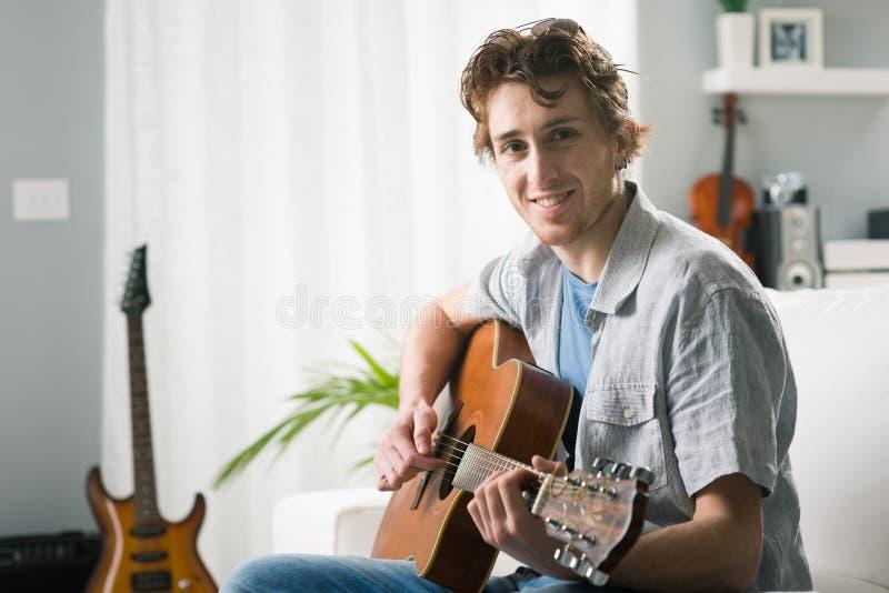 Guitarrista novo em casa imagem de stock royalty free