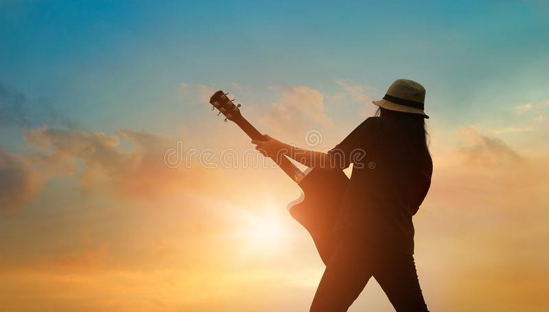 Guitarrista que joga a guitarra acústica no por do sol colorido do cloudscape fotos de stock royalty free
