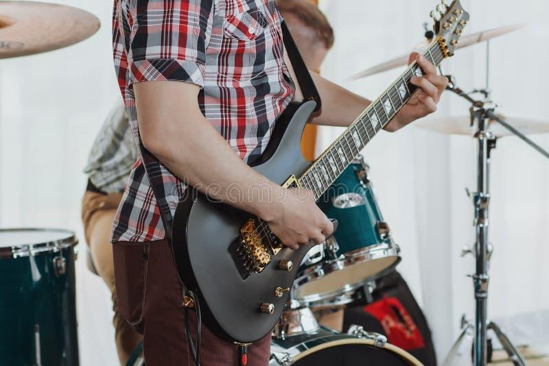 Guitarrista que jogam sua guitarra acústica em um concerto local com sua faixa e um outro guitarrista no fundo imagem de stock