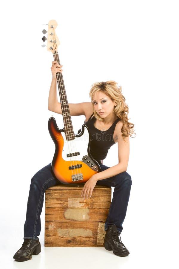 Guitarrista rubio de la mujer de Latina que se sienta en el rectángulo foto de archivo