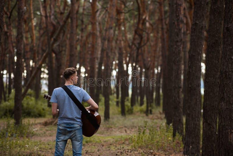 Guitarrista talentoso que juega el bosque que camina concepto imagen de archivo