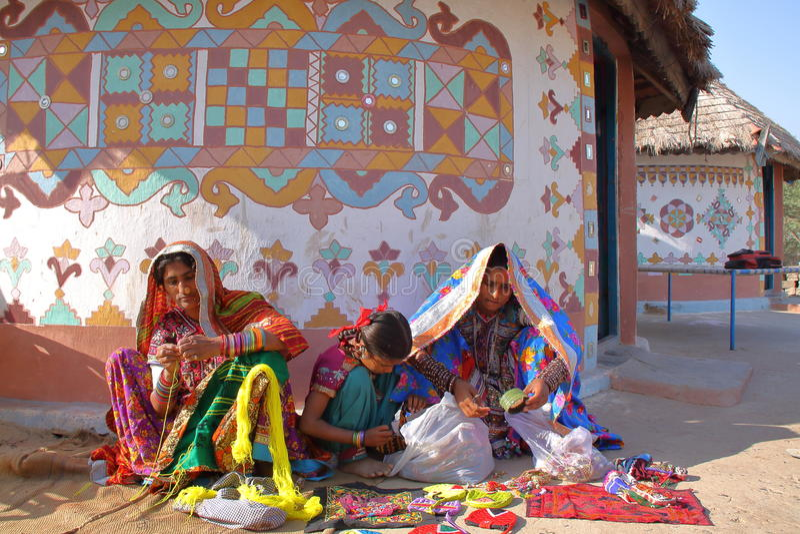 GUJARAT, INDIEN - 20. DEZEMBER 2013: Stammes- Frauen vor ihrem Haus Bhunga in einem lokalen Dorf nahe Bhuj stockbilder