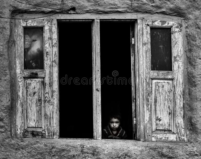 Chid of conflict!. A gujjar boy peeks out through window in a far flung area gujjar-naad qazigund of district anantnag ,kashmir royalty free stock photos