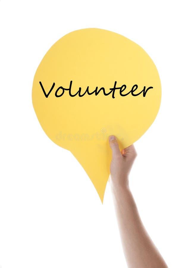 Gul anförandeballong med volontären royaltyfri foto