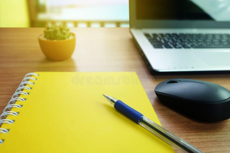 Gul anteckningsbok med tomt utrymme och en penna, med bärbar datordatoren och radiomusen på skrivbordet royaltyfria foton