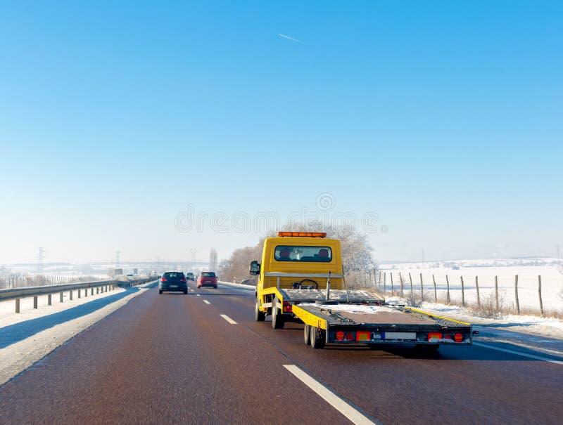 Gul bärgningsbil med tomma plattformflyttningar på huvudvägen i vinter arkivbild