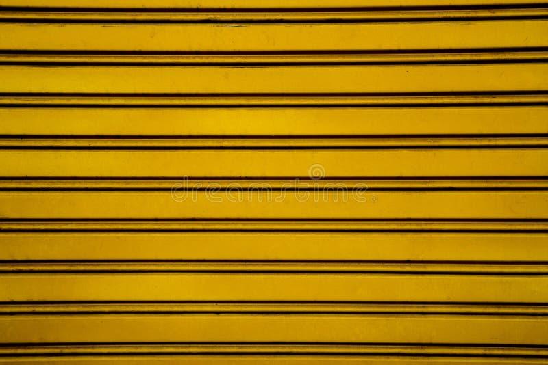 Gul bakgrund för dörr för stålrullslutare (garagedörr med H royaltyfri fotografi