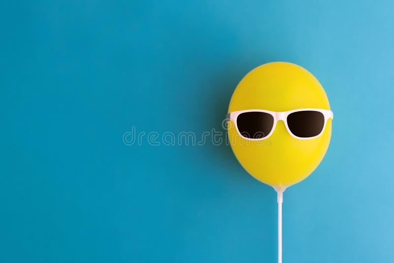 Gul ballong med solglasögon royaltyfri bild