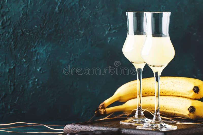 Gul bananlikör i sköt exponeringsglas och nya mogna bananer på tabellen på mörkt - blå bakgrund royaltyfri fotografi