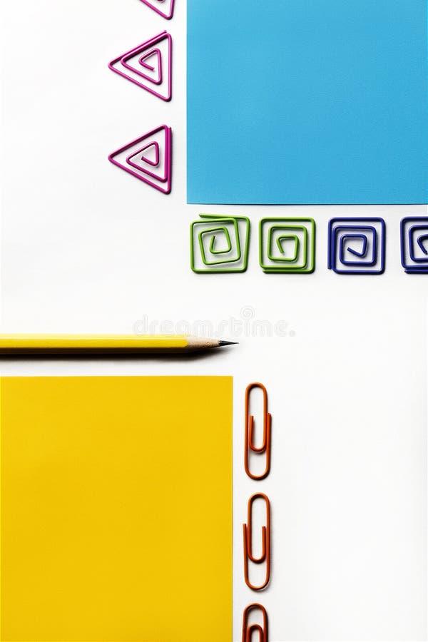 Gul blyertspenna med blått och gult papper och färgrika gem av olika former royaltyfria foton