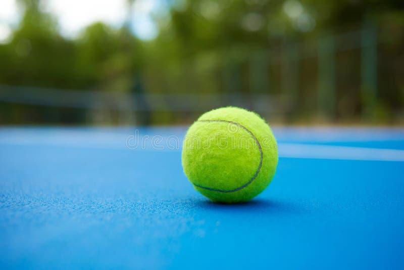 Gul boll på blå tennisbanabakgrund royaltyfria foton