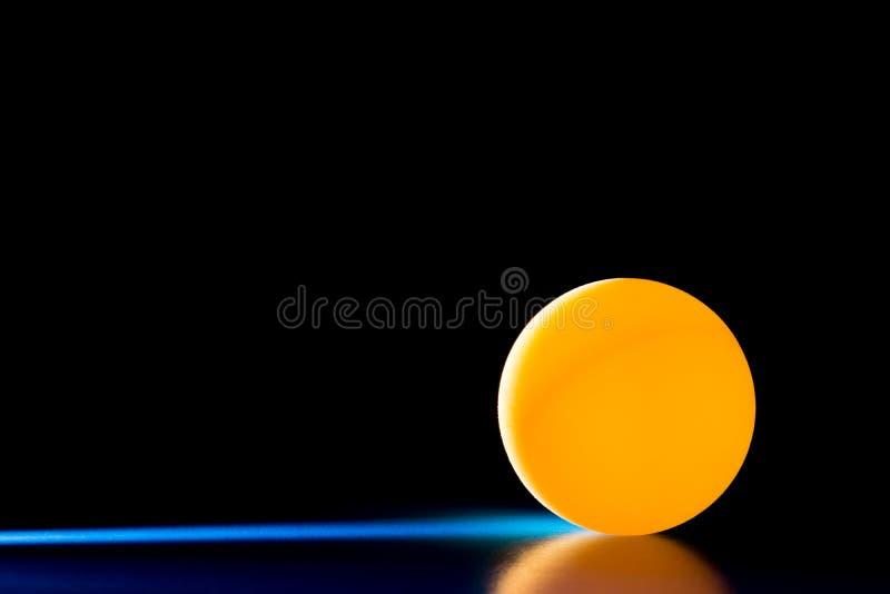 Gul boll på en blå mörk bakgrund som är upplyst vid en sidostråle av ljus royaltyfria bilder