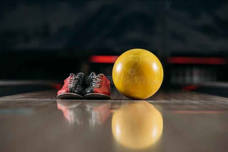 gul bowlingklot med skor på gränden på klubban royaltyfri fotografi