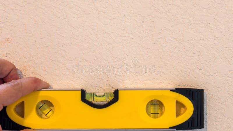 Gul bubbla för visning för bubblanivå i den jämna positionen som indikerar en plan nivå som vilar mot en vit målad vägg arkivfoton
