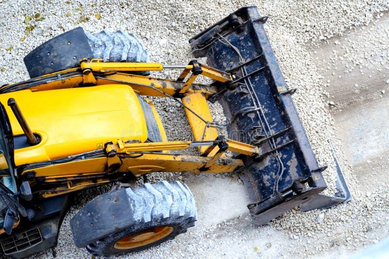 Gul bulldozer som laddar grus för vägkonstruktion arkivbilder