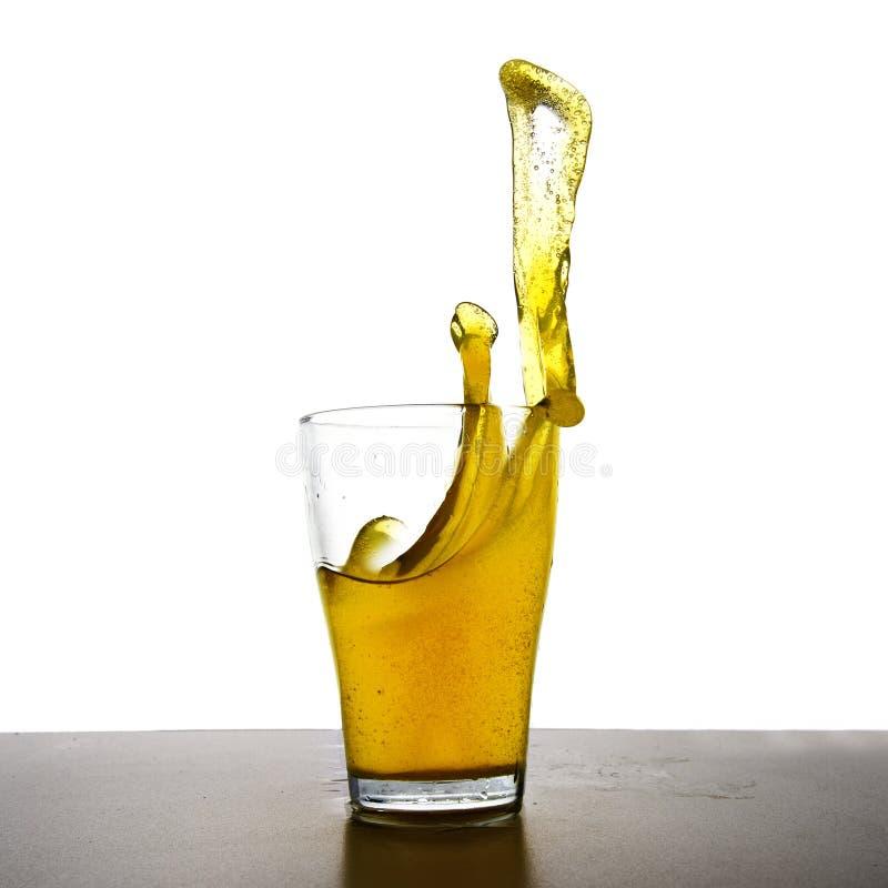 Gul drink med färgstänk i ett exponeringsglas, uppfriskande dryck av lemoen arkivbilder