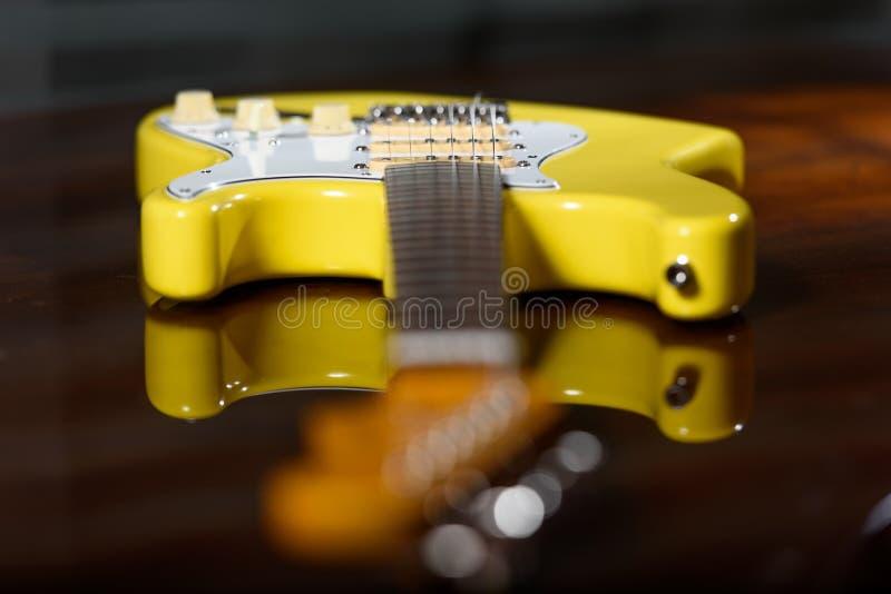 Gul elektrisk gitarr på en träyttersida arkivfoton