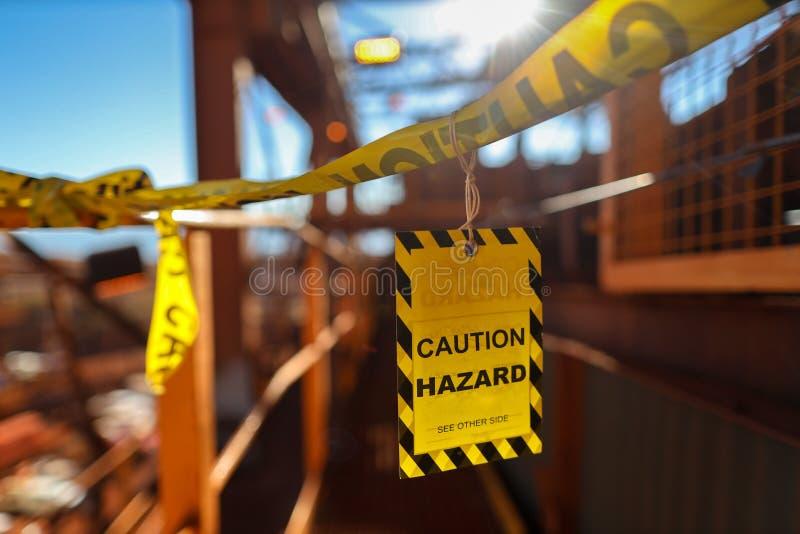 Gul etikett för varningsteckensymboler som applicerar på tillträdeskonstruktionsarbetsplatsen för att se till varnande försiktigh royaltyfri bild