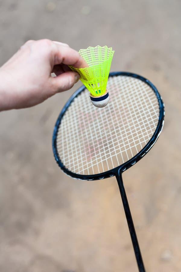 Gul fjäderboll över badmintonracket arkivfoton