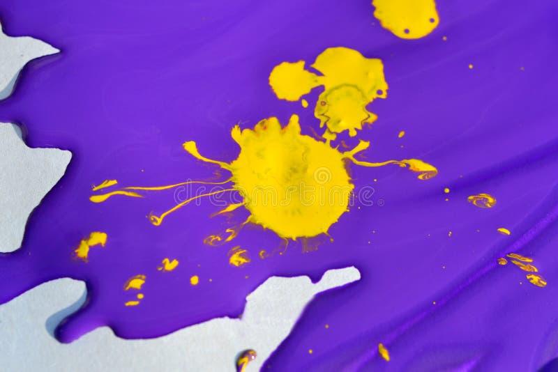 Gul fläck på deliquescent lilamålarfärg arkivfoto