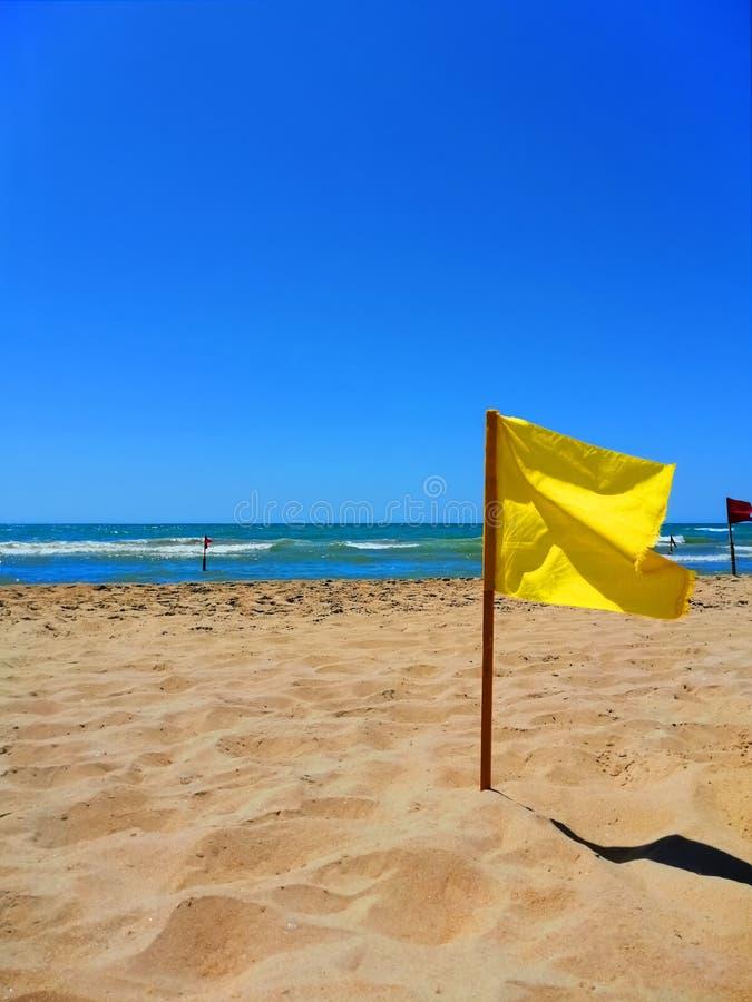 Gul flagga vid havet på en sandig strand royaltyfri fotografi