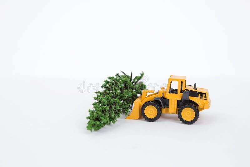 Gul främre laddarlastbil med den gröna trädisolaten på vit bakgrund royaltyfria bilder