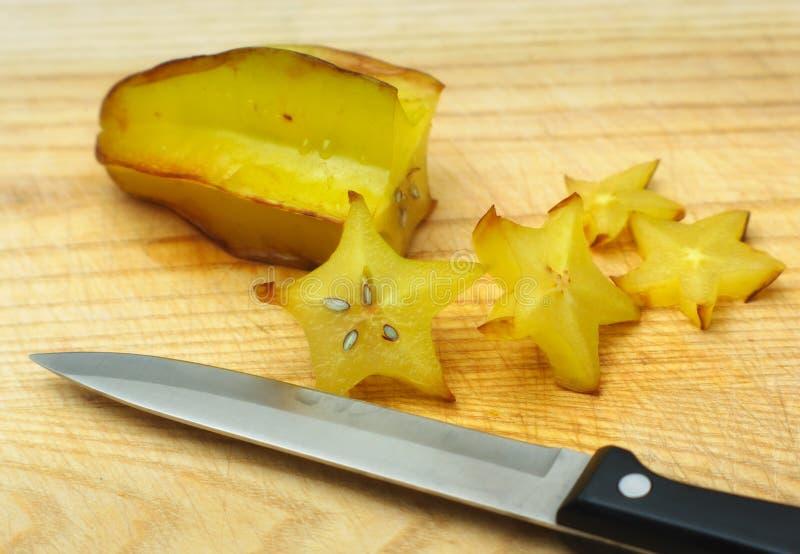 Gul frukt, stjärnafrukt på träplattan med kniven royaltyfri foto