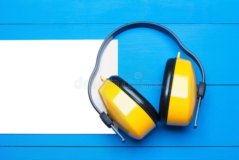 Gul funktionsduglig skyddande hörlurar på målad blå trätabl arkivfoto