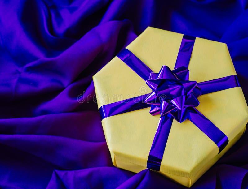 Gul gåvaask med en purpurfärgad pilbåge royaltyfri fotografi
